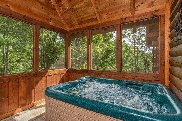 Hot tub on a screened in porch at Mountain Breeze, a 1 bedroom cabin rental located in Pigeon Forge