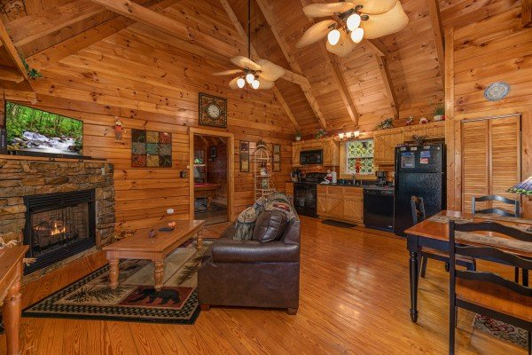 Living room with fireplace and TV at Mountain Breeze, a 1 bedroom cabin rental located in Pigeon Forge