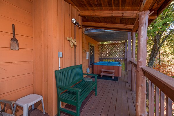 Bench on a covered porch at Hawk's Nest, a 1-bedroom cabin rental located in Pigeon Forge