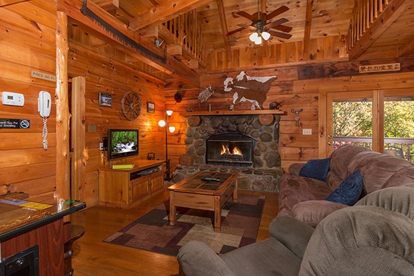 Living room with a fireplace, TV, and deck access at Hawk's Nest, a 1-bedroom cabin rental located in Pigeon Forge