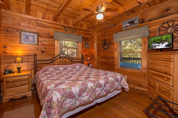King-sized bed and two end tables, dresser, and TV at Hawk's Nest, a 1-bedroom cabin rental located in Pigeon Forge