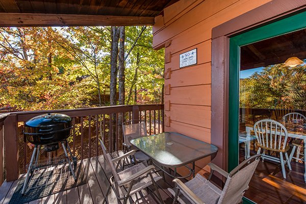 Charcoal grill and dining table on the covered deck at Hawk's Nest, a 1-bedroom cabin rental located in Pigeon Forge