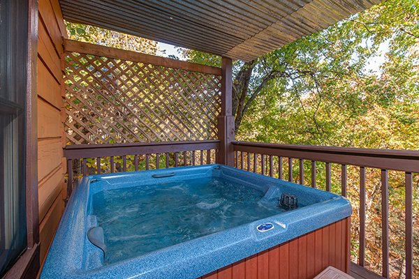 Hot tub with a privacy fence on a covered deck at Hawk's Nest, a 1-bedroom cabin rental located in Pigeon Forge