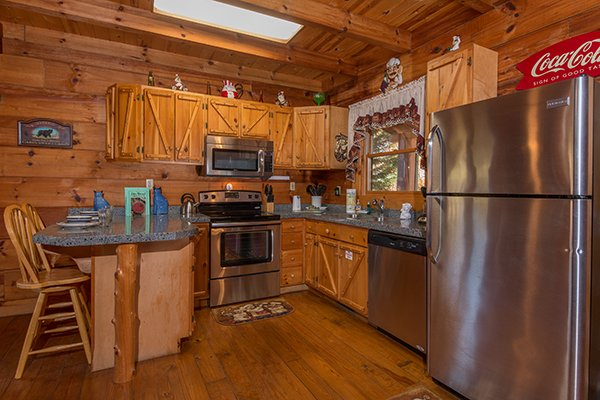 Kitchen with stainless appliances and counter seating for two at Hawk's Nest, a 1-bedroom cabin rental located in Pigeon Forge