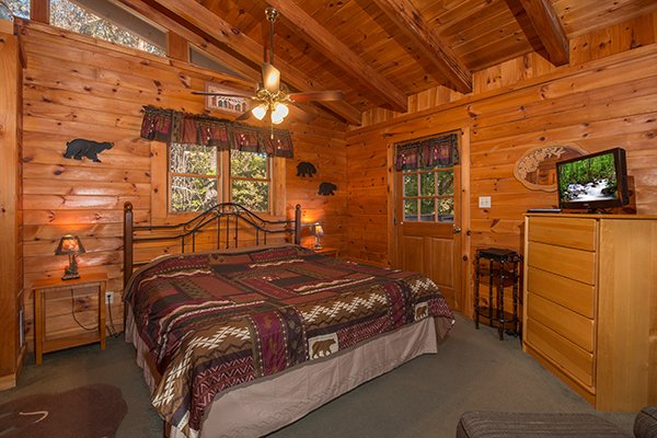 King-sized bed, dresser, and TV in the loft bedroom at Hawk's Nest, a 1-bedroom cabin rental located in Pigeon Forge