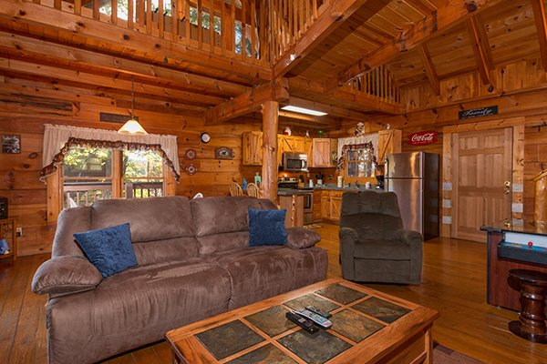 First floor living room, dining space, and kitchen at Hawk's Nest, a 1-bedroom cabin rental located in Pigeon Forge