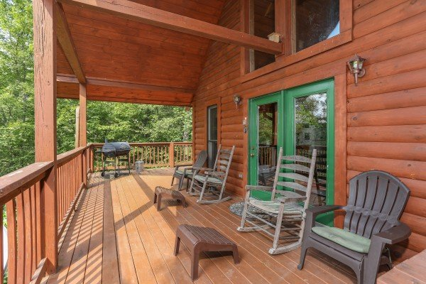 Rocking chairs and Adirondack chairs on the covered deck at Hidden Ecstasy, a 1-bedroom cabin rental located in Pigeon Forge