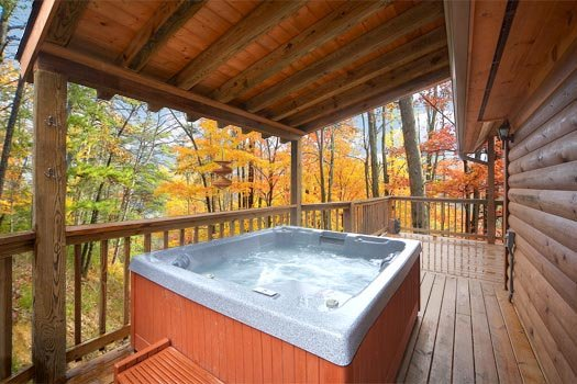 Hot tub on the covered deck at Hidden Ecstasy, a 1-bedroom cabin rental located in Pigeon Forge
