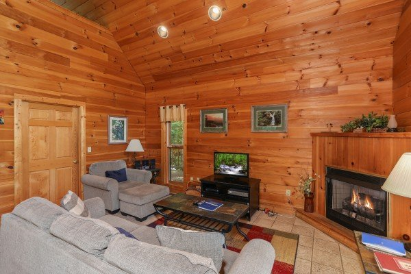 Living room with a TV and fireplace at Hidden Ecstasy, a 1-bedroom cabin rental located in Pigeon Forge