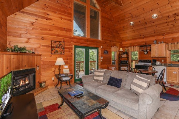 Living, dining, and kitchen space on an open concept main floor at Hidden Ecstasy, a 1-bedroom cabin rental located in Pigeon Forge