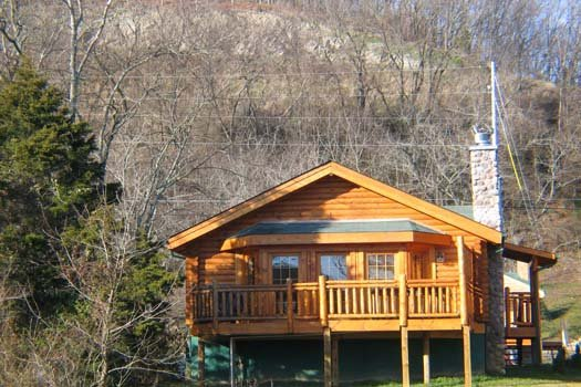 A log cabin with stone stacked chimney called Gone Fishin', a 2-bedroom cabin rental located in Pigeon Forge