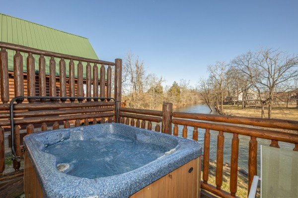 Hot tub overlooking the river at Gone Fishin', a 2-bedroom cabin rental located in Pigeon Forge