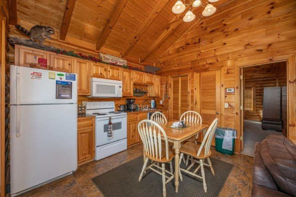 Kitchen with white appliances and dining space for 4 at Gone Fishin', a 2-bedroom cabin rental located in Pigeon Forge