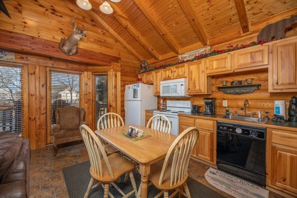 Dining table for four in a kitchen at Gone Fishin', a 2-bedroom cabin rental located in Pigeon Forge