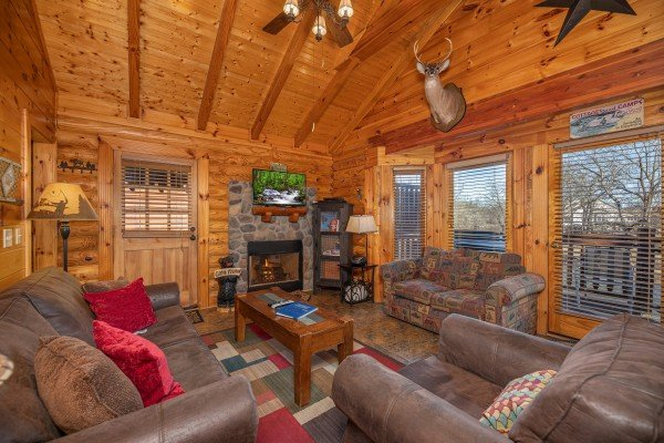 Living room with fireplace, TV, and furniture at Gone Fishin', a 2-bedroom cabin rental located in Pigeon Forge