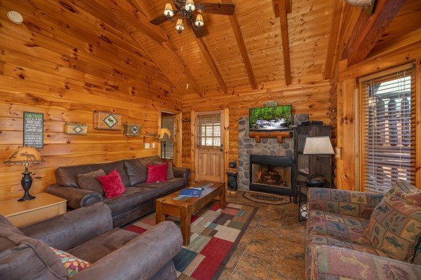 Fireplace, tv, and furniture in the living room at Gone Fishin', a 2-bedroom cabin rental located in Pigeon Forge