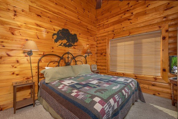 King bed and two night stands in a bedroom at Gone Fishin', a 2-bedroom cabin rental located in Pigeon Forge