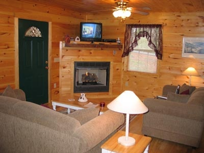 living room with fireplace and tv above at dream catcher a 1 bedroom cabin rental located in pigeon forge