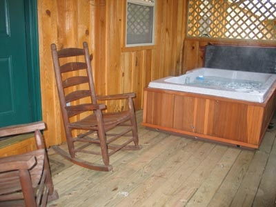 rocking chairs next to the hot tub on the deck at dream catcher a 1 bedroom cabin rental located in pigeon forge