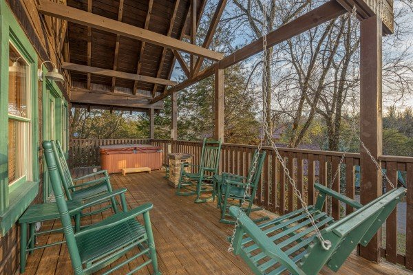 Deck with swing and rocking chairs at Cold Creek Camp, a 3 bedroom cabin rental located in Pigeon Forge