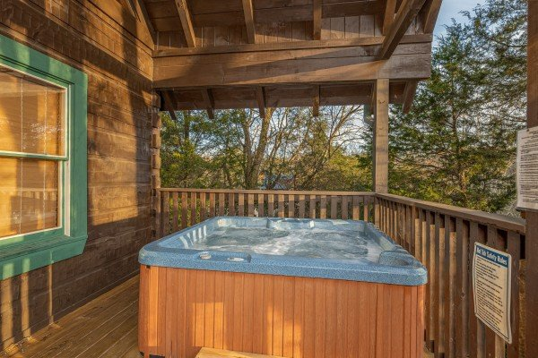 Hot tub on a covered deck at Cold Creek Camp, a 3 bedroom cabin rental located in Pigeon Forge