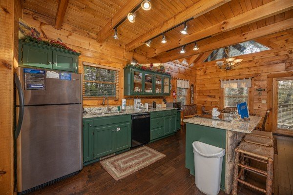 Kitchen with stainless appliances and breakfast bar at Cold Creek Camp, a 3 bedroom cabin rental located in Pigeon Forge