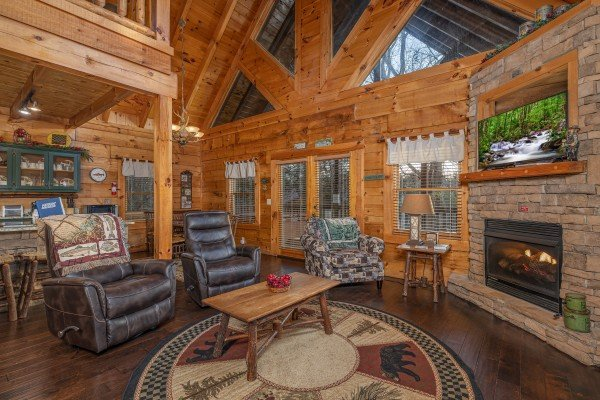 Living room with fireplace and TV and dining space at Cold Creek Camp, a 3 bedroom cabin rental located in Pigeon Forge