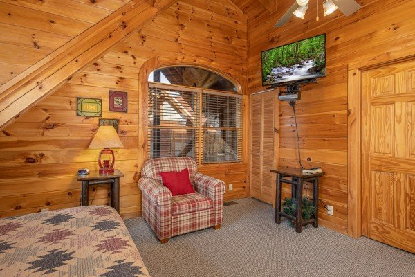 Chair, table, and TV in a bedroom at Cold Creek Camp, a 3 bedroom cabin rental located in Pigeon Forge