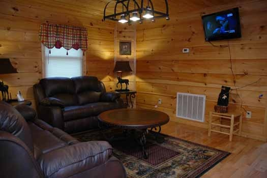 flat screen tv on wall in family room at a great escape a 1 bedroom cabin rental located in pigeon forge