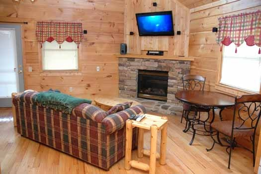 living room with fireplace and sofa bed at a great escape a 1 bedroom cabin rental located in pigeon forge