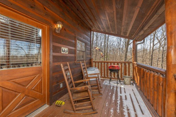Deck rocking chairs and a grill on a covered deck at Honey Bear Haven, a 1 bedroom cabin rental located in Pigeon Forge