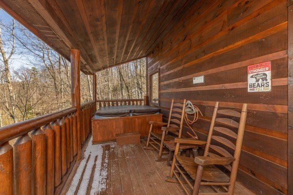 Hot tub and rocking chairs on a covered deck at Honey Bear Haven, a 1 bedroom cabin rental located in Pigeon Forge