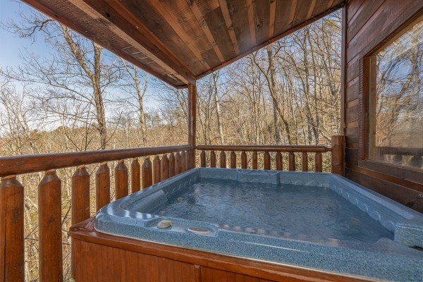 Hot tub on a covered deck at Honey Bear Haven, a 1 bedroom cabin rental located in Pigeon Forge