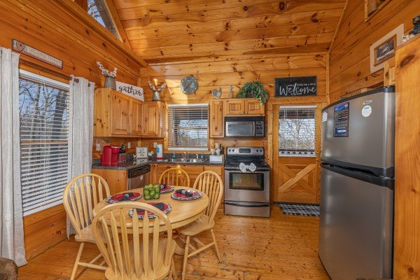 Dining table for four in a kitchen with stainless appliances at Honey Bear Haven, a 1 bedroom cabin rental located in Pigeon Forge