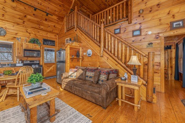 Living room seating, dining space, and kitchen at Honey Bear Haven, a 1 bedroom cabin rental located in Pigeon Forge