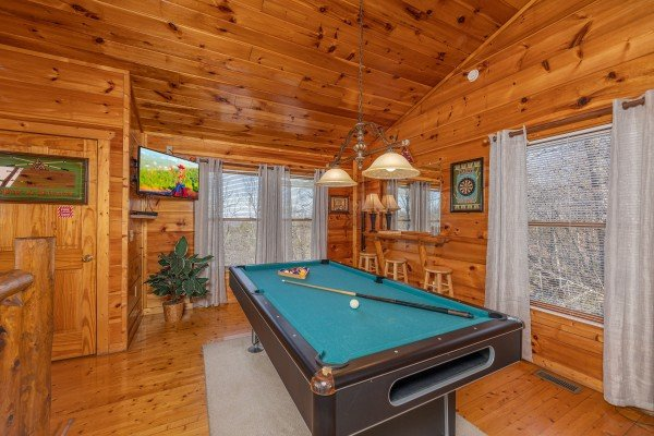 Pool table and TV in the game space at Honey Bear Haven, a 1 bedroom cabin rental located in Pigeon Forge