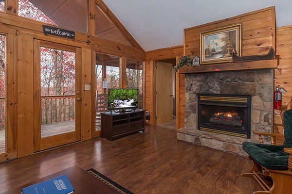Living room with vaulted ceiling, fireplace, TV, and deck access at Mountain Garden, a 2 bedroom cabin rental located in Gatlinburg