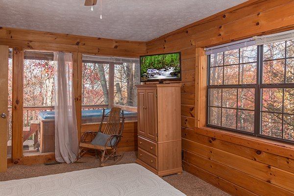 Bedroom with an armoire, TV, and deck access at Mountain Garden, a 2 bedroom cabin rental located in Gatlinburg