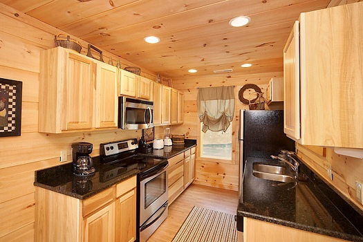 Fully stocked kitchen with stainless appliances at A Perfect Getaway, a 3 bedroom cabin rental located in Pigeon Forge