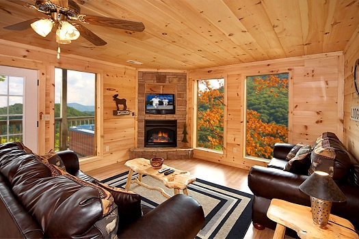 living room with a fireplace and tv mounted above at a perfect getaway a 3 bedroom cabin rental located in pigeon forge