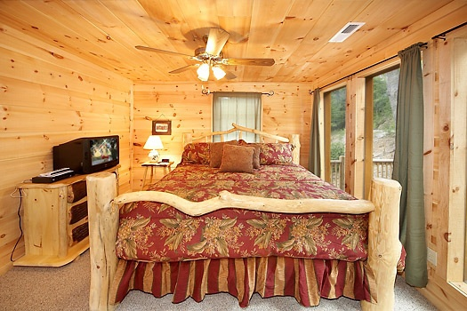king sized bed with tv on the main floor at a perfect getaway a 3 bedroom cabin rental located in pigeon forge
