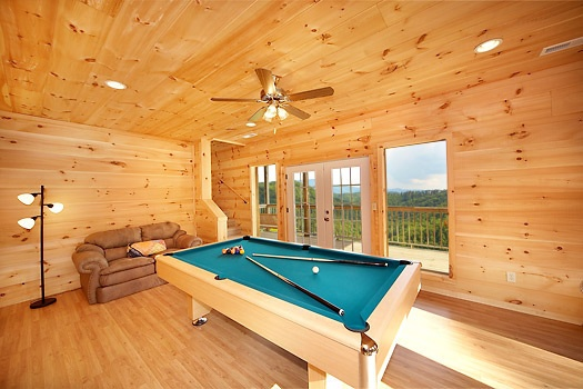 A game room you will enjoy a pool table and sofa seating at A Perfect Getaway, a 3 bedroom cabin rental located in Pigeon Forge