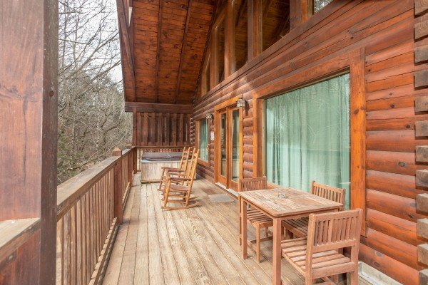Deck with dining set, rocking chairs, and hot tub at Blackberry Delite, a 1-bedroom cabin rental located in Pigeon Forge