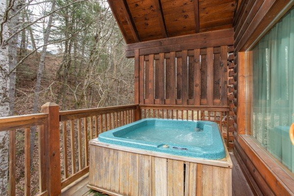 Hot tub on a covered deck at Blackberry Delite, a 1-bedroom cabin rental located in Pigeon Forge