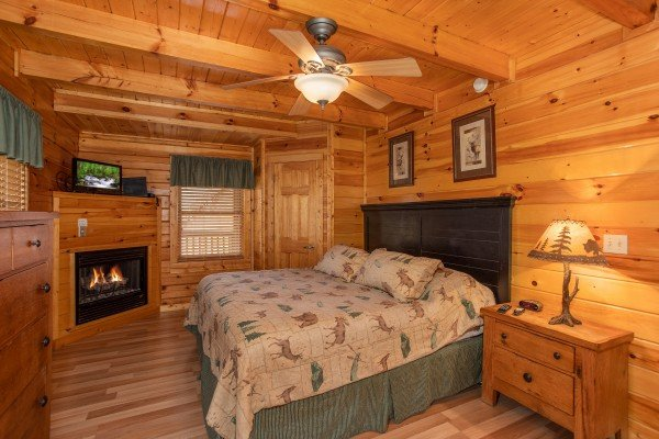 Bedroom with a fireplace and tv at Blackberry Delite, a 1-bedroom cabin rental located in Pigeon Forge