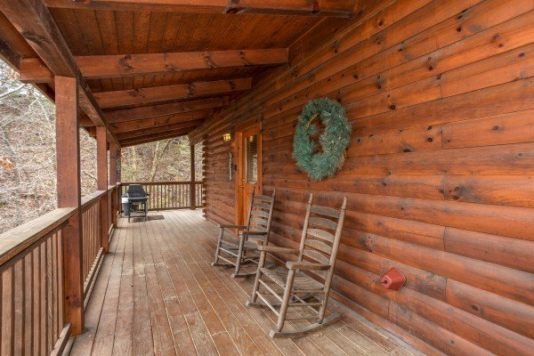Rocking chairs and a grill on the covered deck at Blackberry Delite, a 1-bedroom cabin rental located in Pigeon Forge