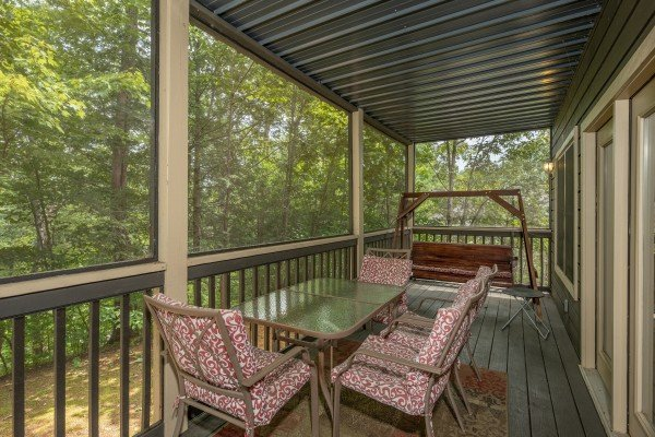 Deck dining and porch swing on a covered deck at Amazing Memories, a 3 bedroom cabin rental located in Pigeon Forge