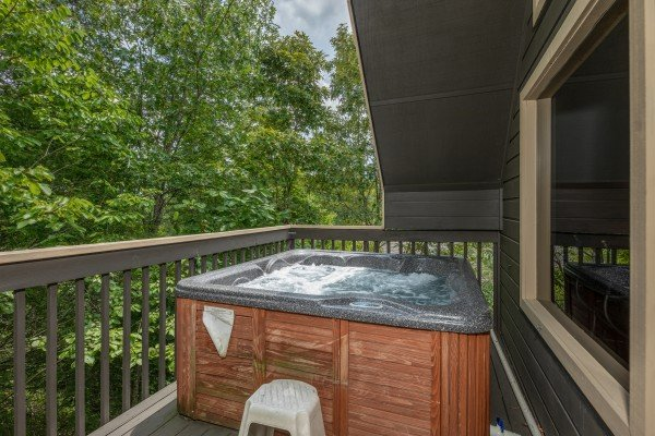 Hot tub on a semi-covered deck at Amazing Memories, a 3 bedroom cabin rental located in Pigeon Forge