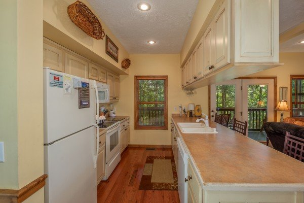 Galley kitchen with white appliances and a breakfast bar at Amazing Memories, a 3 bedroom cabin rental located in Pigeon Forge