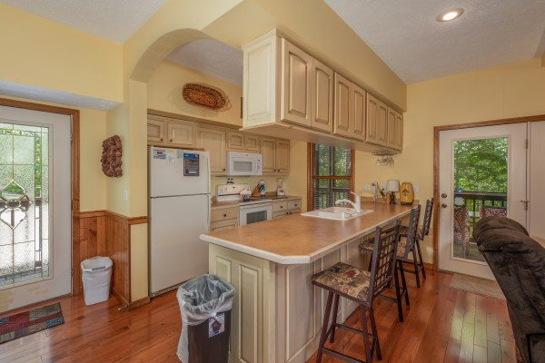Breakfast bar and kitchen with white appliances at Amazing Memories, a 3 bedroom cabin rental located in Pigeon Forge